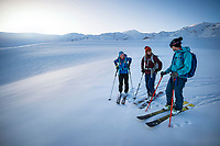Friends stand talking while skiing in the wide open landscape at the Too Ashu Pass area of Kyrgyzstan