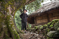 "A Wa elder stands in front of his traditional house in the village of Wengding. The Wa, which literally means ""mountain dwellers"", is the hilltribe that inhabit the Sino-Burmese. Known as one of the last headhunting tribe until mid-twentieth century, their population in both countries now approximately no more than one million. In the homogenous society of modern China, Wa is one of more than 50 officially state-recognized ethnic minorities. They can be found around the southwestern corners of Yunnan province."