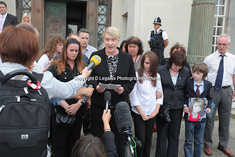 Pictured: Detective Constable for South Wales Police Charmaine Kinson (C) reads a statement on behalf of the family of tragic teen Rebeca Aylward, her mother Sonia is 3rd R  with her other daughter and son Jack who is holding a picture of Rebecca, standing outside Swansea Crown Court. Wednesday 27 July 2011<br />