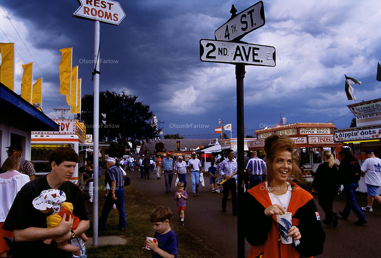 Visitors to the Clay County Fair mingle among scores of food stands in celebration of Iowa's abundance. The fair is known to be the largest agribusiness fair in the country. Street signs are posted so that fairgoers can navigate their way around the grounds.