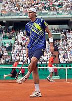 28-05-10, Tennis, France, Paris, Roland Garros, Thiemo de Bakker slaat het gravel uit zijn schoen op de achtergrond  Jo-Wilfriet Tsonga
