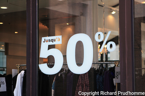up to 50% off everything sale sign in clothing boutique window in downtown Montreal