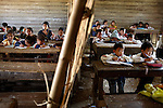 Elementary school classes are divided by a bamboo thatched wall at a village along Highway 13 between Vang Vieng and Luang Prabang, Laos on Tuesday, March 4, 2008.  (photo by Khampha Bouahanh)