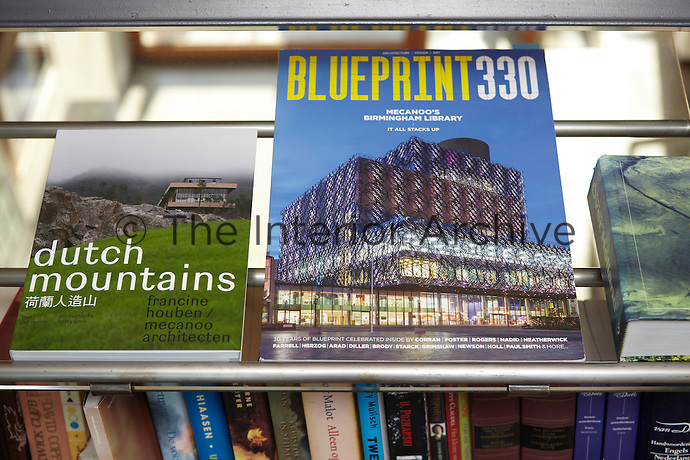 Two books celebrating the work of architect Francine Houben are displayed on a glass shelf.