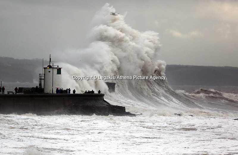 WEATHER PICTURE WALES<br /> Pictured: Wavewatchers gather to watch giant waves crashing against the lighthouse wall in the seaside town of Porthcawl, south Wales, UK. Wednesday 05 February 2014<br /> Re: Strong winds combined with high tides cause flood warnings in many parts of the UK