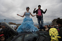 A young woman and her future husband dancing on the top of a car during the Tinsmith gathering on Saint Theodor day. This is also a public announcement for their engagement. These gatherings are like debutant balls, designed to display the eligible girls. But in Bulgaria they are known as 'bride markets' because the tradition requires a 'bride price' or dowry from the boy's family. The gatherings have become controversial since Bulgaria joined the European Union. Women's organizations point out that the girls are kept from school and denied opportunity, other than marrying and being a housewife. Stara Zagora, Bulgaria. He Came on a White Horse.