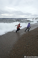 Young kids racing the crashing waves in winter