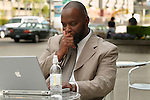 African American man looking thoughtful, working on computer