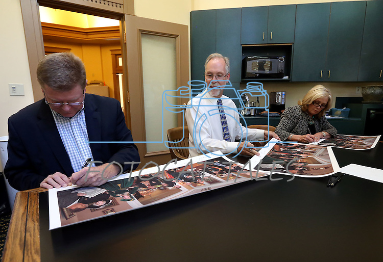 """From left, Congressman Mark Amodei, historian Ron James and former first lady Dema Guinn sign prints of Steven Saylor's """"Nine Cheers for the Silver State"""" artwork, at the Capitol, in Carson City, Nev., on Wednesday, Sept. 24, 2014. Dignitaries featured in the painting will sign the 150 limited edition prints which will be sold as a fundraiser for the Comstock Foundation for History and Culture.<br /> Photo by Cathleen Allison"""