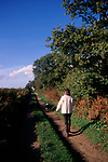 A3A7W1 Woman and collie dog country lane walk Suffolk England