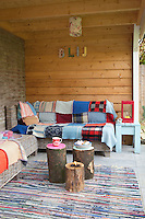 A sheltered outdoor seating area furnished with wicker couches and cushions provides a cosy place to relax in both the summer and the winter months