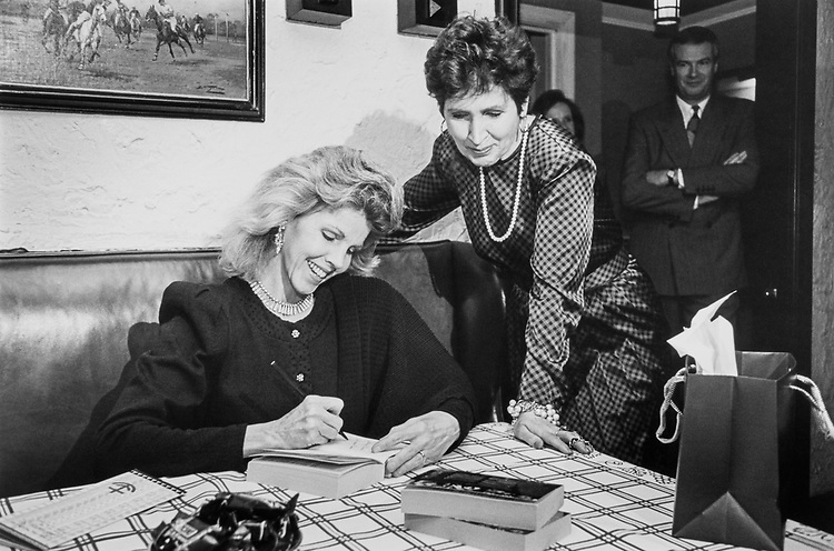 Catherine Mann, wife of Rep. Fred Grandy, R-Iowa signs her book Capitol Hill for Rep. Connie Morella R-Md. at Jockey Club in Riti Carlton in 1992. (Photo by Laura Patterson/CQ Roll Call)