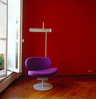 Pillet's 'Sunset Chair' in purple designed for Cappellini stands against a dark red wall in the guest room