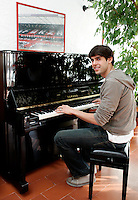 Il fuoriclasse del Milan Ricardo Kaka' ritratto al pianoforte al termine di un'intervista nel centro sportivo di Milanello, 17 marzo 2008. In alto, un poster raffigurante la tifoseria del Milan..AC Milan star Ricardo Kaka' portrayed as he sits at the piano after releasing an interview at the club's sporting center in Milanello, near Milan, 17 march 2008. At top, a poster of AC Milan fans is seen..UPDATE IMAGES PRESS/Riccardo De Luca