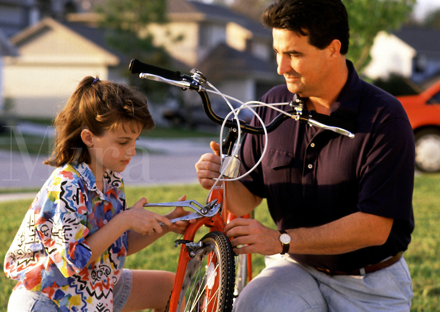 A father and daughter work on bicycle repairs together.
