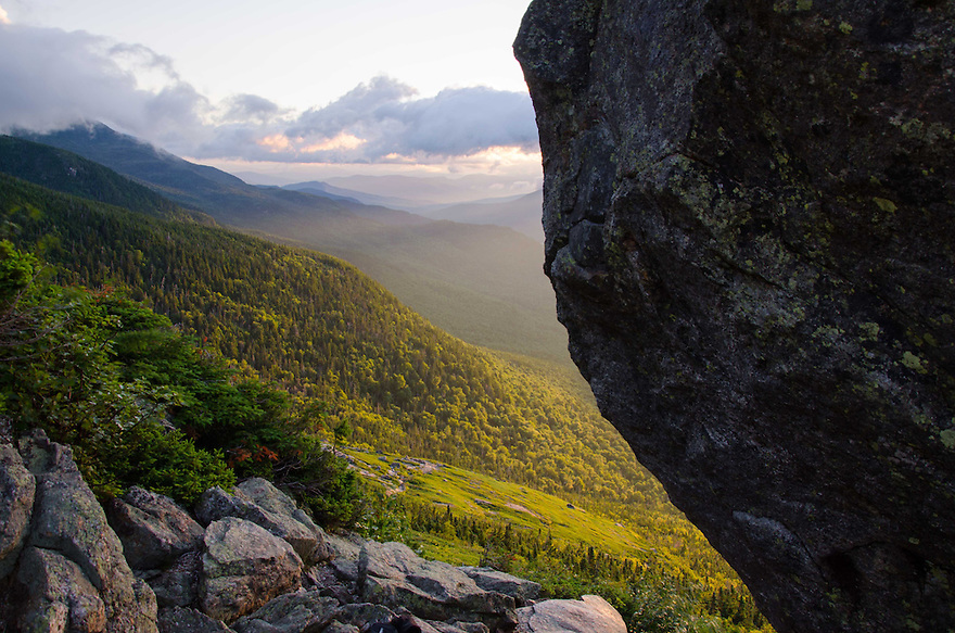 The landscape beyond the rock gets a dose of golden light on the Glen Boulder Trail, in New Hampshires White Mountains.