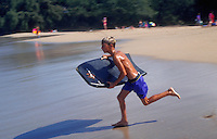 Boy as he runs on the beach holding his boogie board. Hawaii.