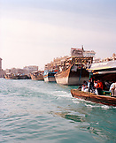 UNITED ARAB EMIRATES, Dubai, people traveling on water taxis along the Dubai Creek with old cargo Dhows in the background