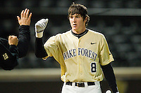 Kevin Conway (8) of the Wake Forest Demon Deacons high fives teammates after scoring a run in the 8th inning against the North Carolina State Wolfpack at Wake Forest Baseball Park on March 15, 2013 in Winston-Salem, North Carolina.  The Wolfpack defeated the Demon Deacons 12-6.  (Brian Westerholt/Four Seam Images)