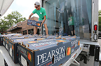 NWA Democrat-Gazette/DAVID GOTTSCHALK Benjamin Sparks, with the Georgia Peach Connection, unloads Friday, July 5, 2019, boxes of peaches at their pop up stand on College Avenue in Fayetteville. The Georgia Peach Connection is on a four week tour selling free stone peaches from Pearson Farm in Fort Valley, Georgia. The Connection will be in Bentonville, Rogers and Fort Smith today.