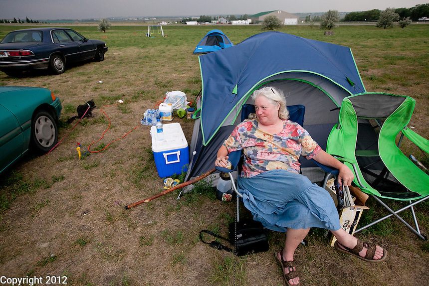 A lady who did not wish to be identified sits outside the tent she shares with her boyfriend in the field.