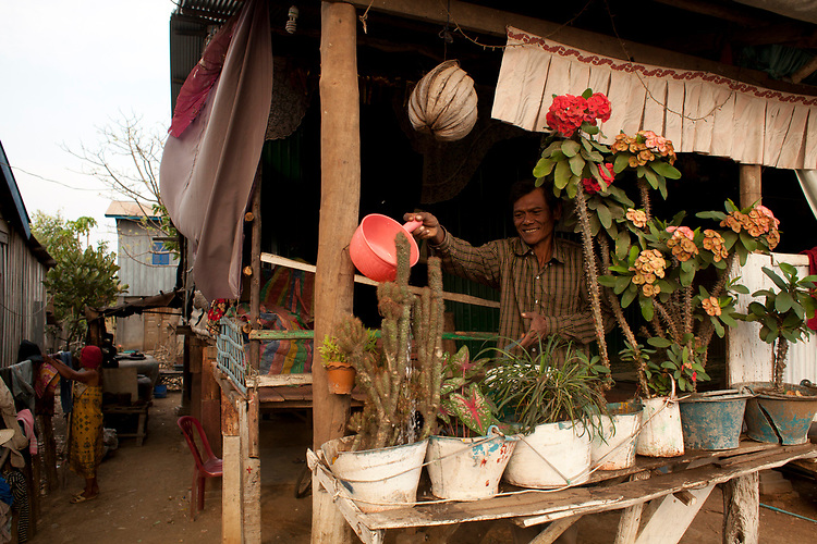 A man waters his house plants in a small village near Battambang, Cambodia. <br /> <br /> Photos &copy; Dennis Drenner 2013.