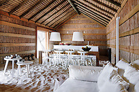 The floor of the living area at CasasNaAreia is covered in fine white sand, which is heated in winter, and the room is furnished with a variety of designer pieces