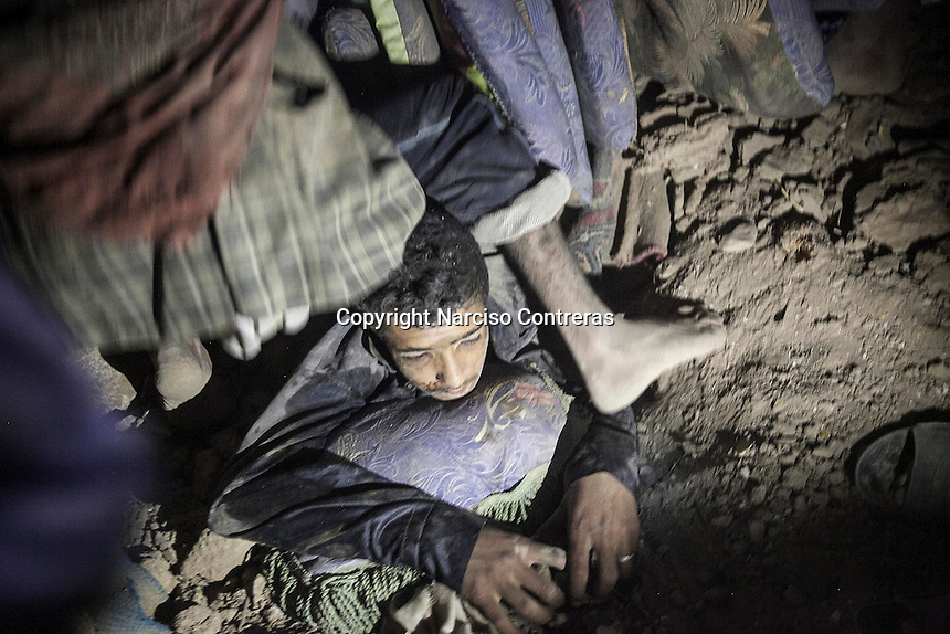 July 15, 2015 - Sa'dah, Yemen: Bashar Al Asadi, 14 years-old, is rescued from the rubble of a house building after it was hit by a fighter jet from the Saudi-led coalition in the northern city of Sa'dah, the stronghold of the Houthi movement in Yemen. His family was buried under the rubble during the attack. Two members of his family, the mother and one brother (not pictured) died from their injuries, while his sister (not pictured) survived. (Photo/Narciso Contreras)