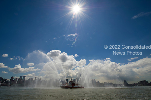 An FDNY fireboat is one of the lead boats for the space shuttle Enterprise as Enterprise is towed by barge up the Hudson River on it's way to the Intrepid Sea, Air and Space Museum where it will be permanently displayed, Wednesday, June 6, 2012 in New York City. .Mandatory Credit: Bill Ingalls / NASA via CNP