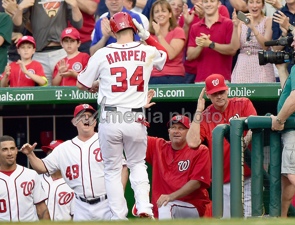 Washington Nationals right fielder Bryce Harper (34) returns to the dugout as manager Matt Williams (9), right, salutes him after connecting for a first inning home run against the New York Yankees at Nationals Park in Washington, D.C. on Tuesday, May 19, 2015. Photo Credit: Ron Sachs/CNP/AdMedia