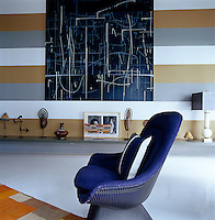 A painting by Jacqueline Humphries hangs on the khaki, grey and white striped wall of the living room