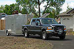 Black Ford Super Duty tows an gun metal enclosed trailer while hauling yard debris and an extension ladder