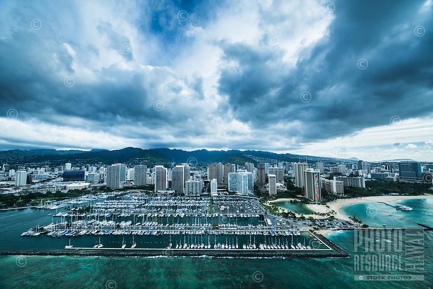 An aerial view of a cloudy sky over Ala Wai Harbor, the Hilton Hawaiian Village's lagoon and Kahanamoku Beach, Waikiki, O'ahu.