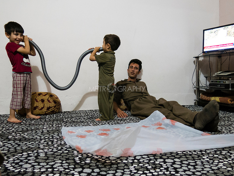 15/08/14  Iraq -- Daquq, Iraq -- Peshraw Omer, a peshmerga fighter from Penjwen sits in his house with his children at the home after returning from the front line in Daquq.
