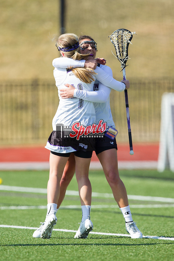 Kendyl Gardner (5) of the High Point Panthers gets a hug from teammate Mackenzie Carroll (4) after scoring a goal against the American University Eagles during first half action at Vert Track, Soccer & Lacrosse Stadium on February 8, 2014 in High Point, North Carolina.  The Panthers defeated the Eagles 11-6.   (Brian Westerholt/Sports On Film)