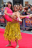 Lizzie Cundy<br /> The &quot;Bula Quo!&quot; UK film premiere, Odeon West End cinema, Leicester Square, London, England.<br /> July 1st, 2013<br /> full length pink flower in hair grass skirt lifting carrying holding funny mouth open<br /> CAP/BF<br /> &copy;Bob Fidgeon/Capital Pictures