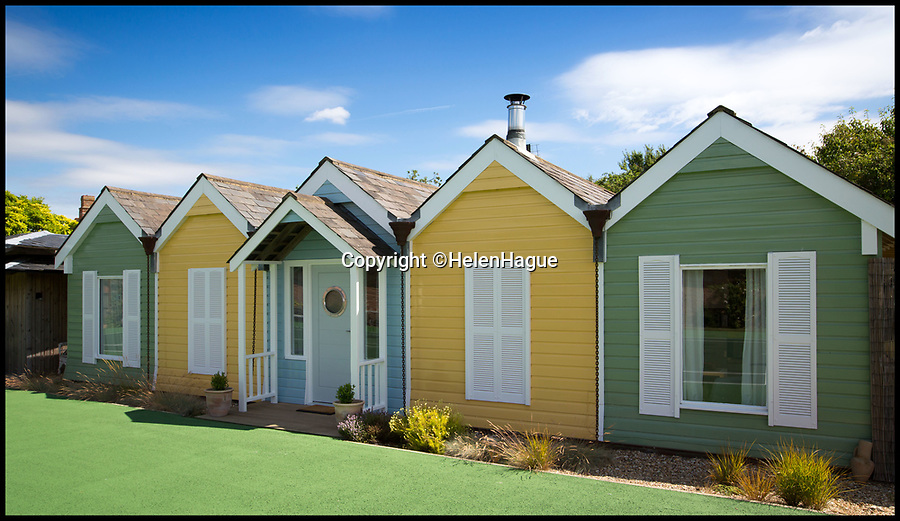 BNPS.co.uk (01202 558833)Pic: HelenHague/BNPS<br /> <br /> Life's a beach...even five miles from the seaside.<br /> <br /> It looks like a quaint row of beach huts found at any seaside resort - but this is actually a quirky eco-home five miles from the nearest beach which people can now rent for up to £1,200 a week.<br /> <br /> Rod Hague and his wife Helen originally built the Beach Huts as their family home and designed a series of pitched roofs so they could maximise the number of solar panels they could fit on the roof.<br /> <br /> When Rod realised the roof design looked like a row of beach huts he decided to paint the house in bright hues to create the seaside effect.<br /> <br /> After eight years living there they now rent the unusual property out and it certainly is a 'holiday' home.