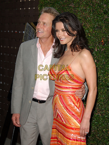 """CATHERINE ZETA-JONES & MICHAEL DOUGLAS.HBO's Los Angeles Premiere of """"A Father...A Son.. Once Upon a Time in Hollywood"""" held at The Academy of Motion Picture Arts and Sciences in Beverly Hills, California.  July 14th, 2005.half length celebrity couple married husband wife grey gray suit orange red sequins striped dress summery arm around waist.www.capitalpictures.com.sales@capitalpictures.com.Supplied By Capital PIctures"""