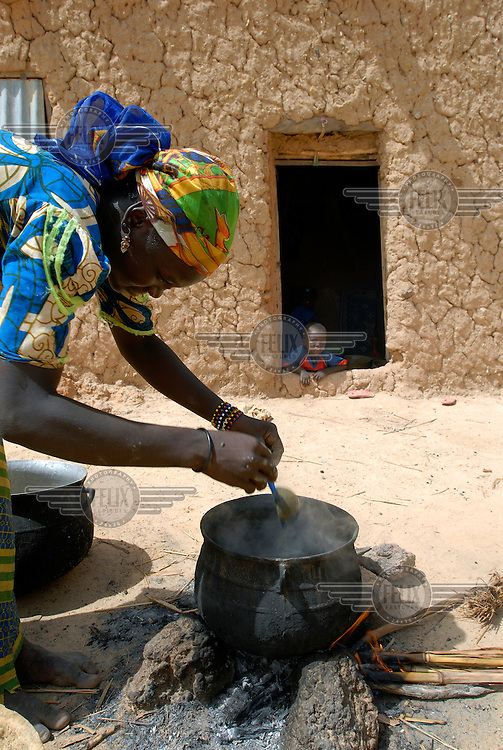 Hinda Salha cooks a meal over a small fire outside her home in Dan Saga village.