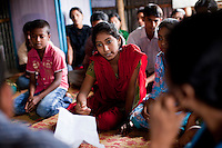 "Tamanna Jinnat (13, red scarf) hands over a list of potential child brides while speaking in a monthly meeting of a Children's Group in Bhashantek Basti (Slum) in Zon H, Dhaka, Bangladesh on 23rd September 2011. Tamanna explains, ""we have an organised system: we have a list of girls who are potential child brides and we check on them. Another initiative is making sure that there is birth registration for babies so that there will be a proof of their age."" Tamanna's mother said that ""at your age, you are not aware of the benefits of an early marriage,"" to which Tamanna replied, ""how about issues of maternal mortality from being too young to bear children?"". She also wants to be allowed to work part time so she can support her own education and independence. The Bhashantek Basti Childrens Group is run by children for children with the facilitation of PLAN Bangladesh and other partner NGOs. Slum children from ages 8 to 17 run the group within their own communities to protect vulnerable children from child related issues such as child marriage. Photo by Suzanne Lee for The Guardian"