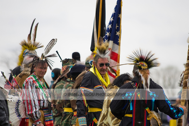 """A group of Native Americans at the intertribal Healing Horse Spirit PowWow in Mt. Airy, Maryland stands at the entrance of the sacred PowWow circle, waiting for the call for the """"Grand Entrance."""" This group includes several U.S. and Vietnam War veterans who bear the American flag and POW-MIA (prisoners of war-missing in action) flag."""