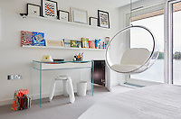 An Eero Aarnio bubble chair hanging from the ceiling is a fun feature in a teenager's bedroom. A low, secret door leads to a sibling's bedroom next door.