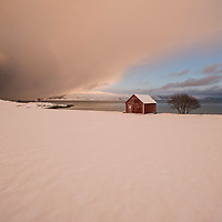Winter scene of red boathouse, Senja, Norway