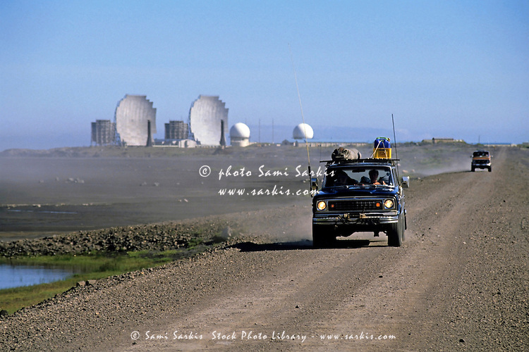 Two four wheel drives travel along a dirt near the NATO base in Stokksnes, Iceland.