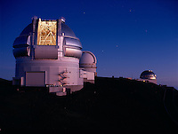Gemini North Telescope (left), University of Hawaii 2.2-meter telescope (behind) and United Kingdom Infrared Telescope (right), with the Southern Cross visible in the sky to the right of Gemini, Mauna Kea, Hawaii