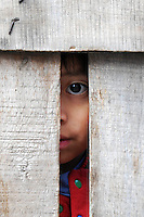 Child looking through fence in Quito, Ecuador.