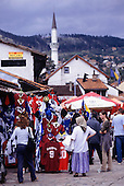 Sarajevo, Bosnia and Herzegovina. The arab quarter (Bascarsija); market; stall selling clothes (t-shirts); minaret.