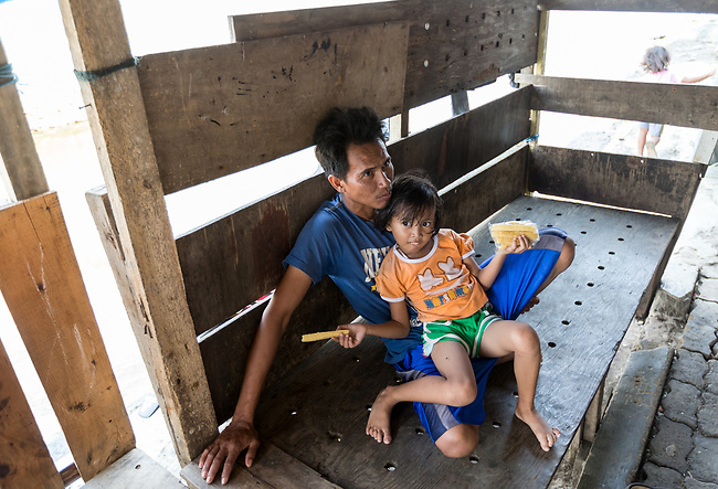 13 August 2019, Jakarta, Indonesia: Facory worker Dodi Riyanto with his daughter Ulfi relaxing above the flooded road in front of his home below the sea wall at Muara Baru, North Jakarta.The protective seawall barrier keeping the ocean at bay was built by Governor (now President) Joko Widodo. It was constructed to prevent further encroachment by the ocean into the settlements in North Jakarta which is sinking at a rate faster than anywhere else in the world. Residents speak of the flooding  that would drive them to higher ground washing away all in its path. Residents now say the land is dry and usable but it is an ongoing crisis for Indonesia. Picture by Graham Crouch/The Telegraph