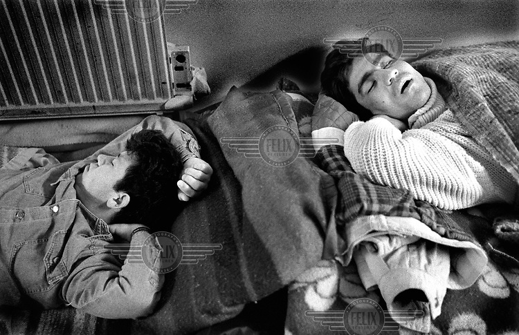 CALAIS, LAST FRONTIER.© 2001 MATIAS COSTA/PANOS..Dreaming of England? Two Afghan refugees, Amir and Behrouz, sleeping at the infamous Sangatte refugee centre run by the Red Cross. They rest during the day so that they have the energy to make an attempt on the Channel Tunnel at night. Some British politicians have called for the centre to be closed down.