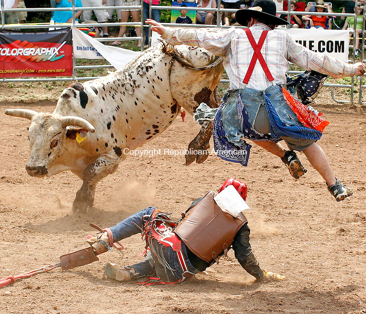 Prospect, CT-05, June 2010-060510CM13 Edwin Chaccu of Guatemala gets thrown of a bull, while Matt Carter, of Tennessee leaps in to help, during the Man Vs. Beast bull riding competition.  The event, held at Senior Poncho's in Prospect, featured top PBR riders from the world circuit.  The event will run again Sunday, from 2-4pm and will feature approximately 32 cowboys.  --Christopher Massa Republican-American